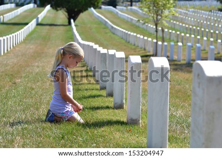 young girl praying in cemetery - stock photo