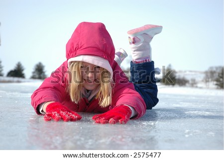 Young Girl Prone on Frozen Lake - stock photo