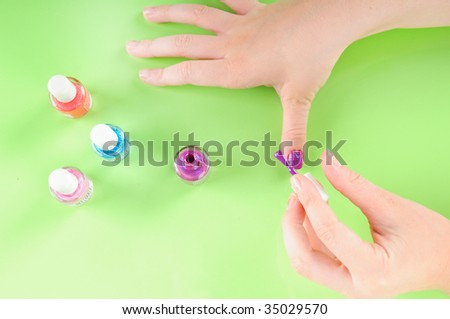 Young girl putting on own purple nail polish - stock photo