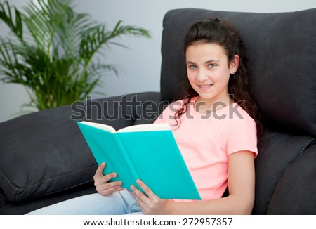 Young girl reading a book on the sofa at home - stock photo