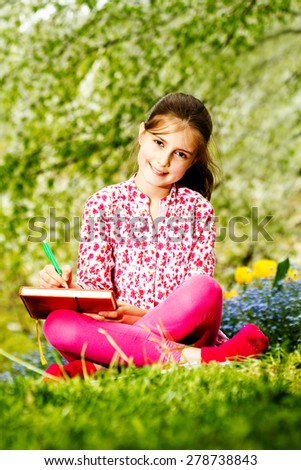 Young girl reading a book outdoors - stock photo