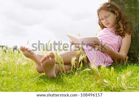 Young girl reading a book while sitting under a tree in the park, smiling. - stock photo