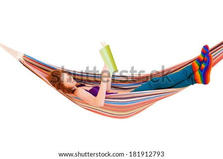 Young girl reading a magazine in a hammock. Isolated on white background - stock photo