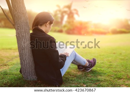 Young girl reading book in park. She is wearing black coat and blue jeans. shallow depth of field, writing spac - stock photo