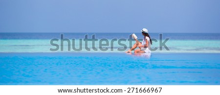 Young girl reading book near swimming pool - stock photo
