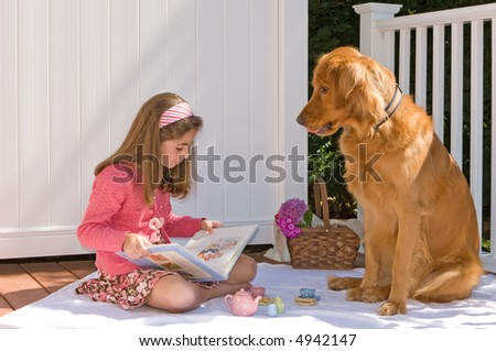 young girl reading to her dog - stock photo