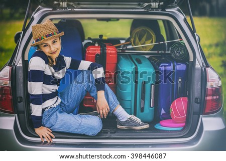 Young girl ready to travel for family vacation sitting in the car (filtered) - stock photo