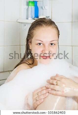 Young girl relaxing with foam in bath - stock photo