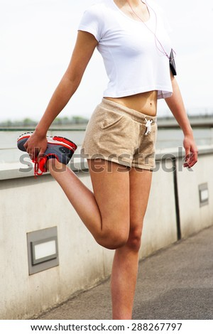 Young girl resting by wall. Jogging outfit. - stock photo