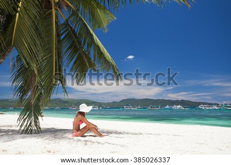 young girl resting on the beach under a palm tree - stock photo