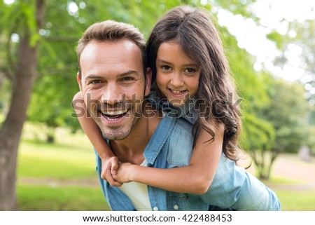 Young girl rides piggyback on her fathers shoulders in the park - stock photo