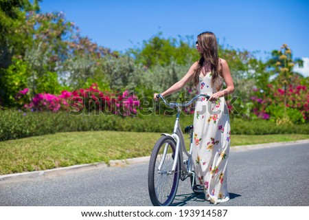 Young girl riding a bike on tropical resort - stock photo