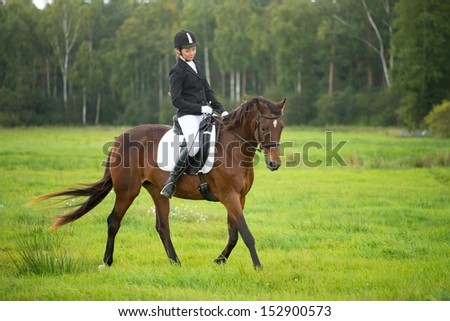 Young girl riding her brown horse outdoors  - stock photo