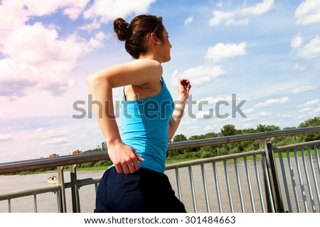 young girl running in thr city, over the river by the bridge, back view. - stock photo