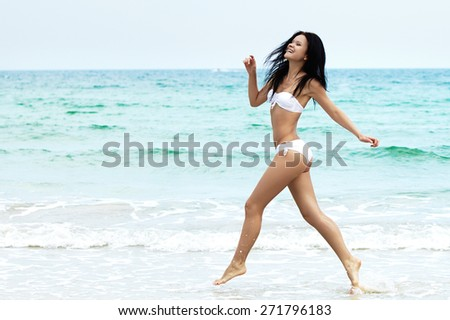 Young girl running on beach. Athletic happy woman jogging in white bikini enjoying the sun exercising. Healthy lifestyle. Fun walk along the shore. Perfect fitness body shapes and tan skin - stock photo