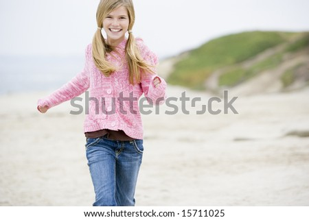 Young girl running on beach smiling - stock photo