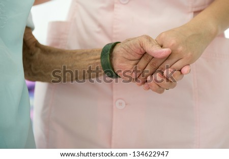 Young girl's hand touches and holds an old woman's wrinkled hands. - stock photo