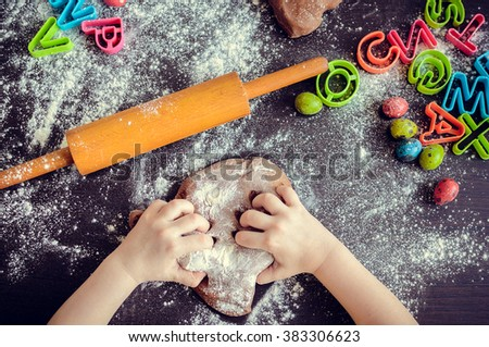 Young girl's hands kneading dough. Easter baking preparation. Close-up of child's hands baking cookies. Easter eggs. Easter food concept. Top view. - stock photo