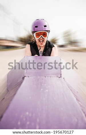 young girl screaming as she's rolling down a hill in a homemade soap-box car - stock photo
