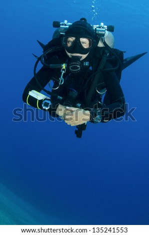 young girl  scuba dives in clear blue water - stock photo