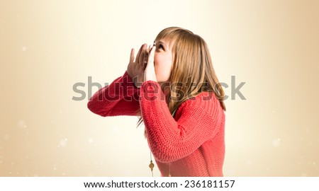 Young girl shouting over ocher background  - stock photo