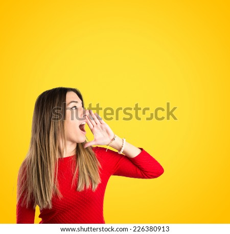 Young girl shouting over yellow background  - stock photo
