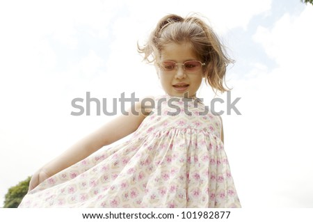 Young girl showing off her dress and wearing pink shades. - stock photo