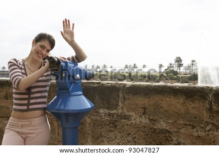 Young girl sightseeing at a city observatory, waving at the camera. - stock photo
