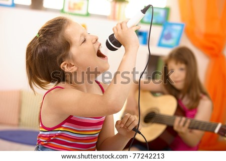 Young girl singing with microphone at home, concentrating, other girl playing guitar in background.? - stock photo