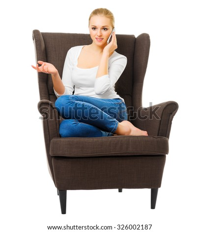 Young girl sit on chair and talking by mobile phone isolated - stock photo
