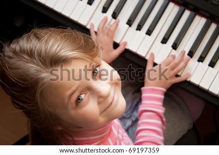 Young girl sitiing at digital  piano - stock photo