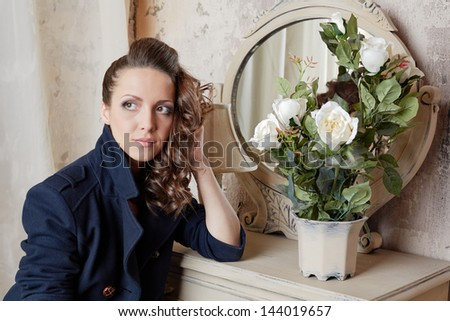 Young girl sits with dreamy look at table with mirror and flowerpot with bunch of white roses - stock photo
