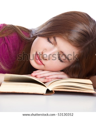 Young girl sitting at the desk and sleeping on a book. Isolated on white background - stock photo