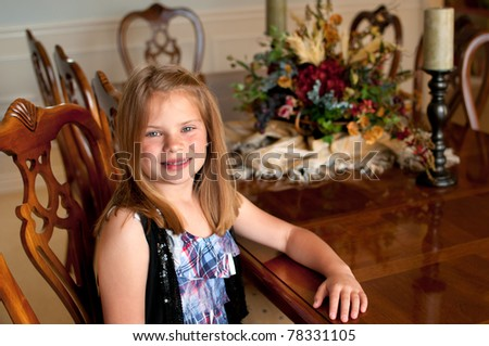 Young girl sitting at wood finished dining room table with decorations - stock photo