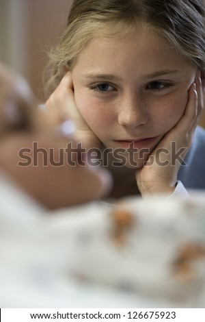 Young girl sitting by hospital bed - stock photo
