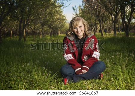 Young girl sitting in orchard looking very natural wearing letterman - stock photo