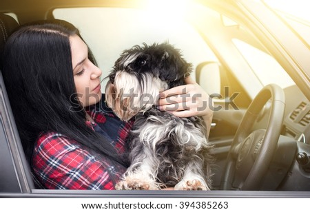 Young girl sitting in the car with her lovely dog - stock photo