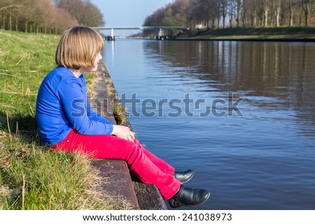 Young girl sitting near waterfront of river - stock photo