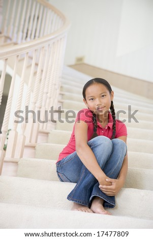Young Girl Sitting On A Stairwell At Home - stock photo