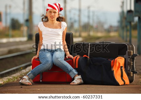Young girl sitting on luggage and waiting for train in the station - stock photo