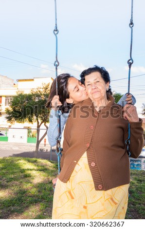 Young girl sitting on swing kissing grandmothers cheek, happily posing for camera. - stock photo
