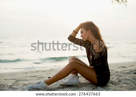 Young girl sitting on the beach after sunset in the sea background.Young traveler.Wear clothes for a hike,camouflage Sweatshirt and sneakers.Dreaming,summer denim clothes,tan girl, - stock photo