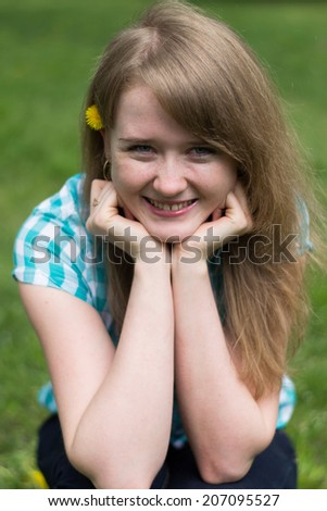 young girl sitting on the grass with a flower in her hair - stock photo