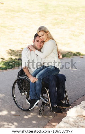 Young girl sitting on the lap of her boyfriend in a wheelchair in the park - stock photo