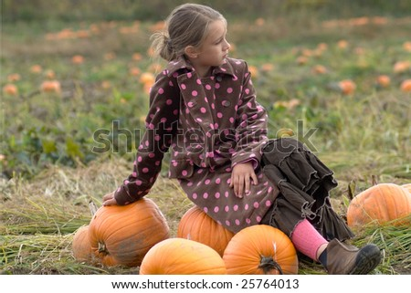 Young girl sitting on the pumpkins in the middle of a pumpkin field in Vermont - stock photo