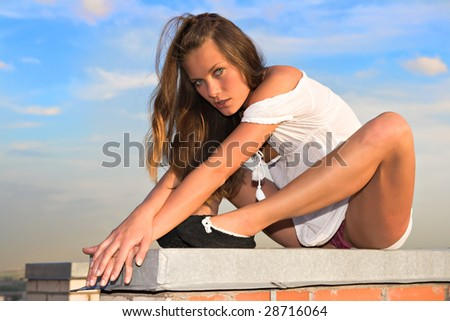young girl sitting on the roof of a skyscraper - stock photo