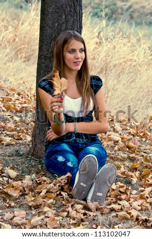 Young girl sitting on the yellow leaves under tree - stock photo
