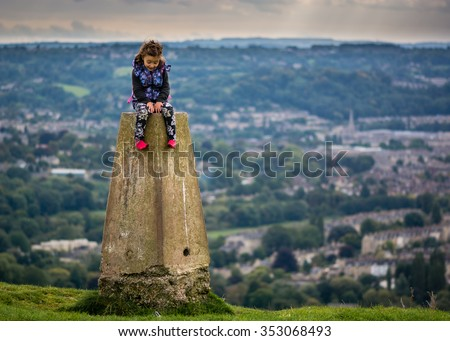 Young girl sitting on triangulation point on Little Solsbury Hill, overlooking the World Heritage City of Bath, Somerset, UK  - stock photo