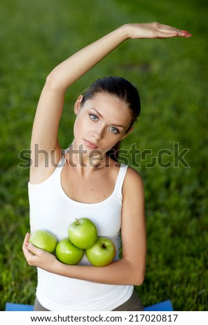Young girl sitting on yoga mat and holding an apple while outdoors in a park - stock photo