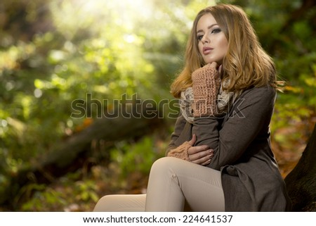 Young girl sitting outdoor in autumn scenery.  - stock photo